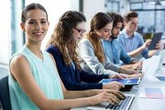 Uśmiechnięta biznes drużyna pracuje na laptopie i cyfrowej pastylce w spotkaniu Zdjęcia Stock