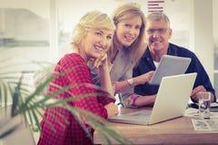 Uśmiechnięta biznes drużyna pracuje na pastylce i laptopie Fotografia Royalty Free
