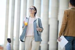 Uśmiechnięta biznesowa dama chodzi blisko budynku biurowego obrazy royalty free