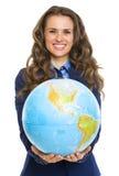 Uśmiechnięta biznesowa kobieta daje ziemskiej kuli ziemskiej Zdjęcie Royalty Free