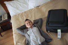 Uśmiechnięta biznesowa kobieta kłaść na łóżku w pokoju hotelowym Zdjęcia Stock