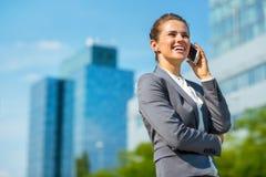 Uśmiechnięta biznesowa kobieta opowiada telefon komórkowego w biurowym okręgu Obraz Stock