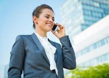 Uśmiechnięta biznesowa kobieta opowiada telefon komórkowego w biurowym okręgu Zdjęcie Royalty Free