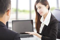 Uśmiechnięta Biznesowa kobieta pokazuje przy laptopem i wyjaśnia plan Zdjęcie Stock