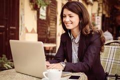 Uśmiechnięta biznesowa kobieta pracuje na laptopie przy kawiarnią Zdjęcie Stock
