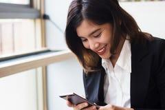 Uśmiechnięta biznesowa kobieta używa smartphone sztuki grę lub socjalny sieć Pojęcie technologia i ludzie Obrazy Stock