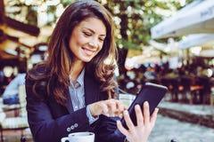 Uśmiechnięta biznesowa kobieta używa technologię Obrazy Stock