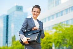 Uśmiechnięta biznesowa kobieta w biurowego okręgu mienia teczce Zdjęcie Stock