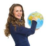 Uśmiechnięta biznesowa kobieta wskazuje w ziemskiej kuli ziemskiej Zdjęcia Stock
