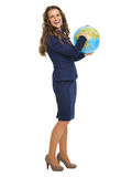 Uśmiechnięta biznesowa kobieta wskazuje w ziemskiej kuli ziemskiej Obrazy Royalty Free
