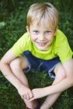Uśmiechnięta blond chłopiec siedzi na trawie w zielonej koszulce i skrótach Fotografia Royalty Free