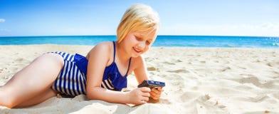 Uśmiechnięta blond dziewczyna na seashore viewing fotografiach na kamerze Obrazy Royalty Free