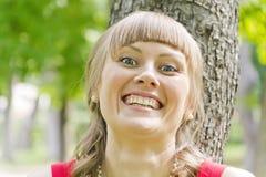 Uśmiechnięta blond dziewczyna z wybrzuszać ona oczy Obrazy Stock