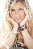 Uśmiechnięta blond szczęśliwa dziewczyna przy dennym lying on the beach na plaży Dwa ręki pod ona twarz Obraz Royalty Free