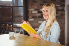 Uśmiechnięta blondynka obraca stronę żółta książka Fotografia Royalty Free