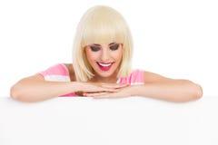Uśmiechnięta blondynka opiera na czytaniu i sztandarze Obrazy Stock