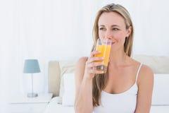 Uśmiechnięta blondynka pije szkło sok pomarańczowy Zdjęcia Stock