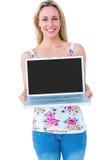 Uśmiechnięta blondynka przedstawia jej laptop Zdjęcia Royalty Free