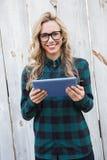 Uśmiechnięta blondynka używa cyfrową pastylkę Zdjęcia Royalty Free