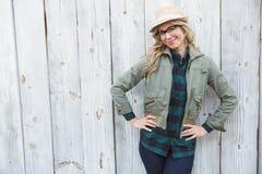 Uśmiechnięta blondynka w kapeluszu pozuje z rękami na biodrach Obrazy Royalty Free