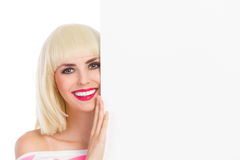 Uśmiechnięta blondynki dziewczyna za plakatem Obraz Stock
