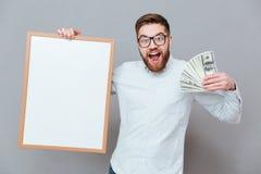 Uśmiechnięta brodata biznesmena mienia copyspace deska i pieniądze Fotografia Royalty Free