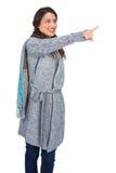 Uśmiechnięta brunetka jest ubranym zimę odziewa wskazywać out Obraz Stock