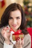 Uśmiechnięta brunetka otwiera prezent na święto bożęgo narodzenia Obrazy Stock