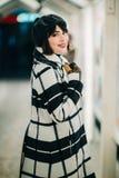 Uśmiechnięta brunetka w żakiecie i czarnym kapeluszu na spacerze przeciw tłu budynek zdjęcie stock