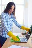 Uśmiechnięta brunetka w koszula i rękawiczkach odkurza laptop Zdjęcie Stock