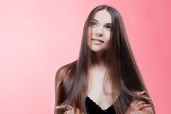 Uśmiechnięta brunetka z perfect włosy, portret na różowym tle obraz royalty free