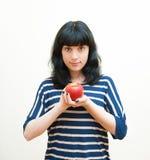 Uśmiechnięta brunetki dziewczyna pokazuje czerwonemu jabłku w ona ręki Obraz Royalty Free