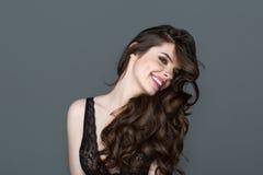Uśmiechnięta brunetki kobieta z długie włosy Fala kędziorów fryzura Włosiany salon Model z błyszczącym włosy obraz stock