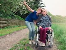 Uśmiechnięta córka i babcia z wózkiem inwalidzkim zdjęcie royalty free