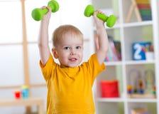 Uśmiechnięta chłopiec ćwiczy z dumbbells Zdrowy życia i sporta pojęcie Fotografia Royalty Free