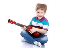 Uśmiechnięta chłopiec bawić się gitarę obraz royalty free