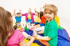 Uśmiechnięta chłopiec bawić się okrąg gry z przyjaciółmi obraz stock