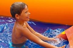 Uśmiechnięta chłopiec blisko waterslide. fotografia royalty free