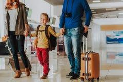 Uśmiechnięta chłopiec czekać na odjazd z rodzicami przy lotniskiem obrazy royalty free