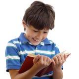 Uśmiechnięta chłopiec czyta książkę Fotografia Royalty Free
