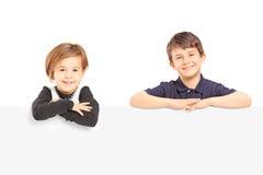 Uśmiechnięta chłopiec i dziewczyna pozuje za pustym panelem fotografia stock