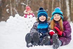 Uśmiechnięta chłopiec i dziewczyna siedzimy w pobliżu na śniegu zdjęcia stock