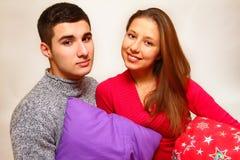 Uśmiechnięta chłopiec i dziewczyna z Bożenarodzeniowymi poduszkami na białych półdupkach Fotografia Royalty Free