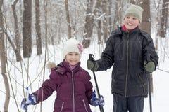 Uśmiechnięta chłopiec i jego siostrzany stojak z narciarskimi słupami Zdjęcia Royalty Free