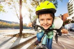 Uśmiechnięta chłopiec jedzie jego w zbawczym hełmie rower Obrazy Royalty Free