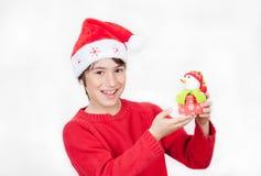 Uśmiechnięta chłopiec jest ubranym Bożenarodzeniowego kapelusz pokazuje prezent, odizolowywającego na wh Zdjęcie Royalty Free