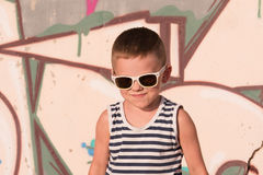 Uśmiechnięta chłopiec jest ubranym okulary przeciwsłonecznych i pasiastą koszula na graffiti tle fotografia stock