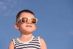 Uśmiechnięta chłopiec jest ubranym okulary przeciwsłonecznych i pasiastą koszula na niebieskiego nieba tle Obraz Stock
