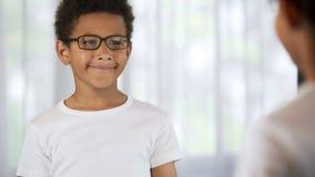 Uśmiechnięta chłopiec jest ubranym szkła, szczęśliwych z dobrym wzrokiem, okulistyka zdjęcia royalty free