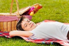 Uśmiechnięta chłopiec kłaść na trawie obok pyknicznego kosza fotografia stock